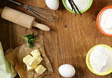 Ingredients for pastry - butter, milk, eggs, flour and vanilla sugar on a wooden background