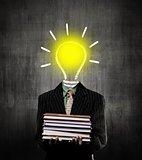 Ideas Bulb Man Holding Books Wearing Suit, Near Chalkboard
