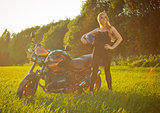 Beautiful girl with a motorcycle in the sun