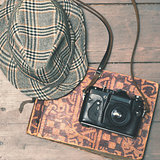 retro camera with vintage trilby hat and photo album on wooden b