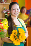 Pretty Woman in Flower Shop with Sunflowers