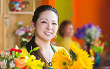 Smiling Woman in Flower Shop with Sunflowers