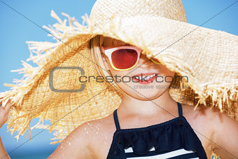 Portrait of happy girl wearing big straw hat