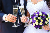 Bride and groom are holding champagne glasses and a bridal bouqu