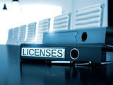 Licenses on Office Binder. Toned Image.