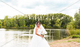 bride in a white dress with  wedding bouquet at the lake