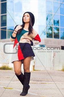 Beautiful young woman staying near building