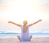 woman with hands up at sunrise beach