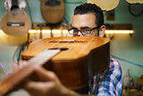 Lute Maker Checking Bridge And Arm Of Classic Guitar