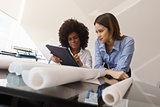 Women Architect Designers With Tablet PC And Blueprints