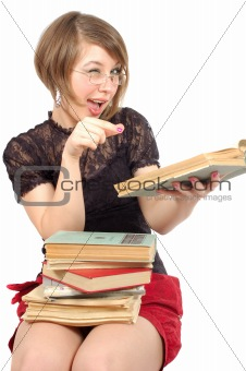 attractive girl sitting with heap of the books and give a wink