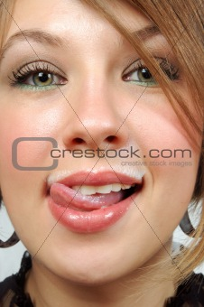 Fresh and beautiful girl with milk moustache, licking lips