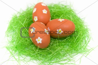 Three red easter eggs with green grass