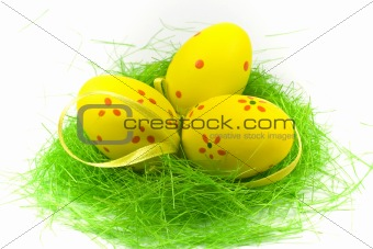 Three yellow easter eggs with green grass