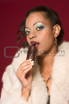 Girl in fur coat eat chocolate