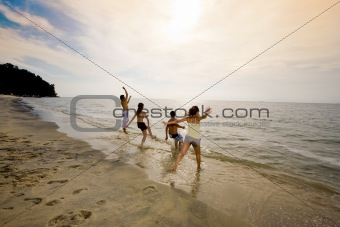 group of friends jumping at the sunset beach