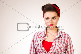 Beautiful young woman with pin-up make-up and hairstyle posing over pink background
