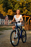Young cute lady posing on a bike in the park