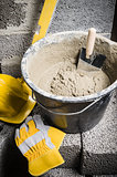 Tools for bricklayer bucket with a solution and a trowel, close-