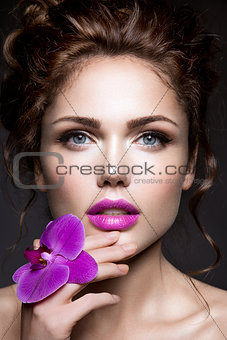 Beautiful girl with violet flower.