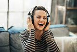 Happy young woman listening music in loft apartment