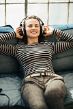 Happy young woman listening to the music through headphones