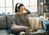 Happy young woman in headphones choosing track on tablet PC