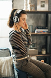 Woman listening to music through headphones in loft apartment