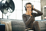 Woman in headphones singing into a microphone in loft apartment