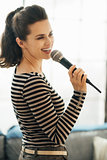 Happy young woman singing into a microphone in loft apartment