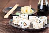 Uramaki sushi with carrot, cucumber, surimi and roasted white se