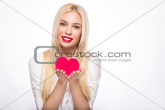 Portrait of Beautiful blond woman with bright makeup and red heart in hand. valentines day