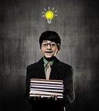 IDEA. Genius Boy Holding Books Wearing Glasses, Smiling Near Cha