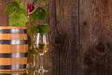 Glass of wine with barrel white bottle behind grapeleaves