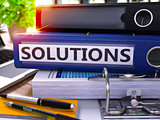 Solutions on Blue Ring Binder. Blurred, Toned Image.