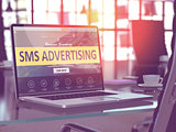 SMS Advertising on Laptop in Modern Workplace Background.