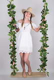 full-length Beautiful young leggy blonde in a little white dress and white cowboy hat on a swing, wooden swing suspended from a rope hemp, rope wrapped vine and ivy