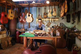 Portrait Of Happy Artisan Lute Maker In Guitar Shop Smiling At C