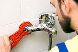 plumber installing water tap in bathroom