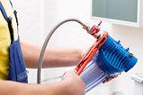 plumber installing new water filter in bathroom