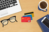 Realistic workplace with three credit cards concept of online payment and shopping