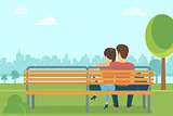 Couple outdoors in the park sitting on bench and looking forward