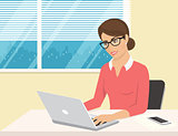 Business woman wearing rose shirt sitting in the office and working with laptop