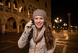 Smiling woman tourist talking cell phone on Piazza San Marco