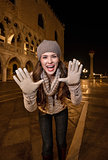 Cheerful woman shouting through megaphone shaped hands in Venice