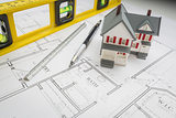 Model Home, Level, Pencil and Ruler Resting on House Plans