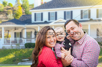 Young Family With Baby Outdoors In Front of Custom Home