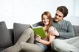 Young  couple with book in apartment interior