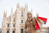 Smiling woman with shopping bags standing in the front of Duomo
