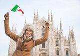 Happy woman tourist with Italian flag rejoicing near Duomo
